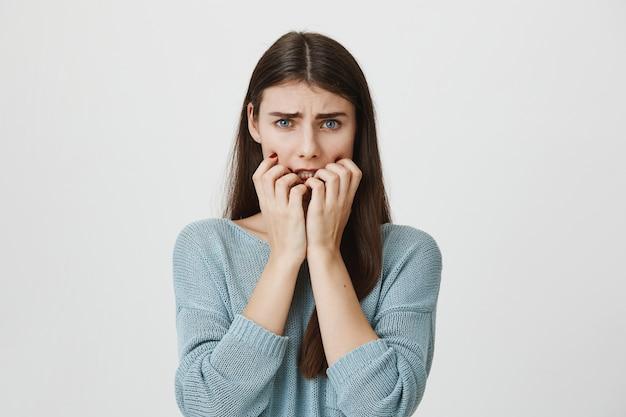 怖がって驚いた女性が爪を噛んで怖がって顔をしかめ