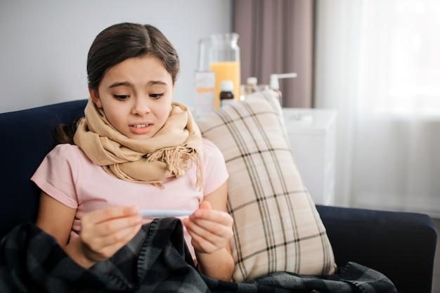 怖いとおびえた小さな女の子が手で温度計を見てください。彼女は一人で家にいます。彼女の喉はスカーフで覆われている。
