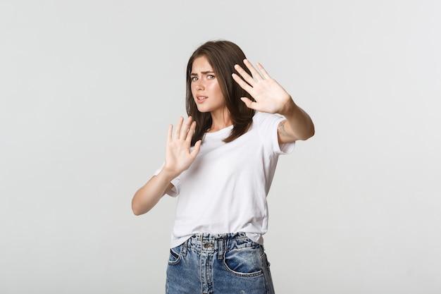 Испуганная и неуверенная в себе милая девушка поднимает руки в жесте остановки, защищаясь.