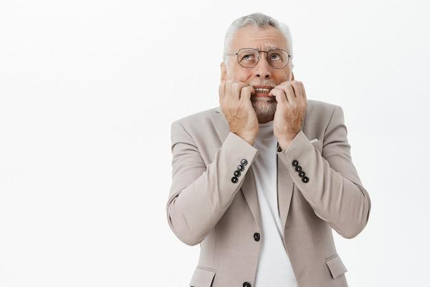 Испуганный и шокированный пожилой мужчина кусает ногти и выглядит встревоженным