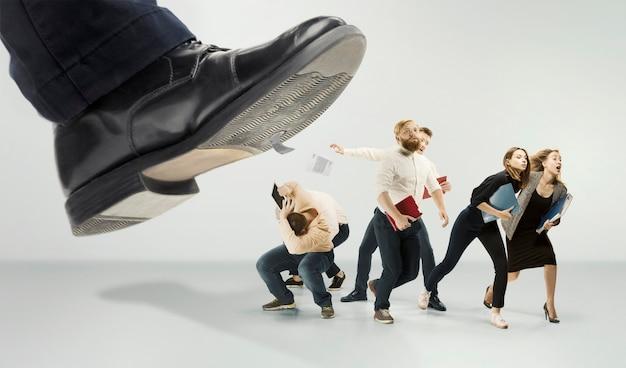 Испуганная и шокированная команда молодых деловых мужчин и женщин под давлением босса