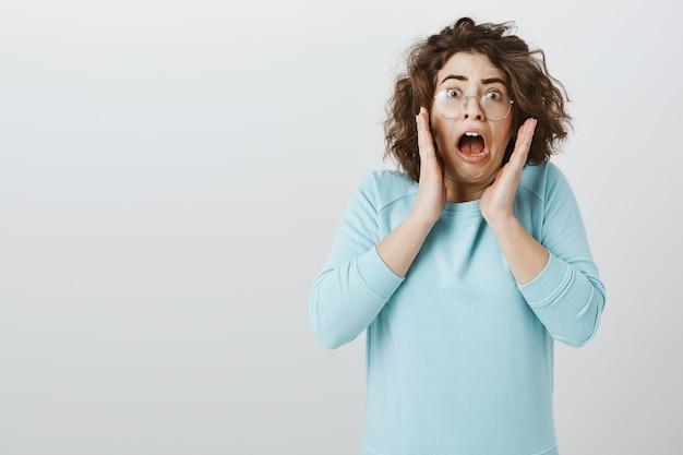 恐怖で叫んで、怖がって探しているメガネの怖いとびっくりした若い女性