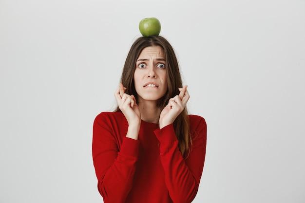 Испуганная и взволнованная девушка скрещивает пальцы, держа на голове зеленое яблоко