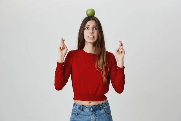 Испуганная и взволнованная девушка с яблочной мишенью на голове молится, скрестив пальцы, опасаясь опасности