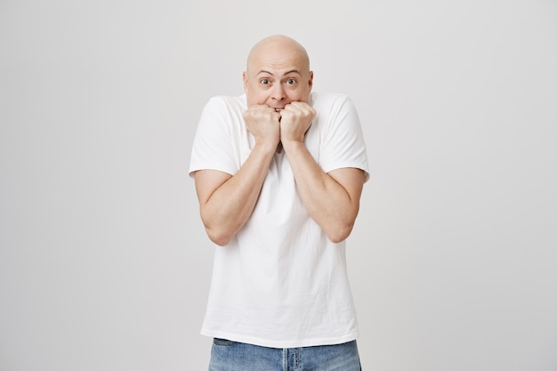 Scared anxious bald guy biting fingernails and looking