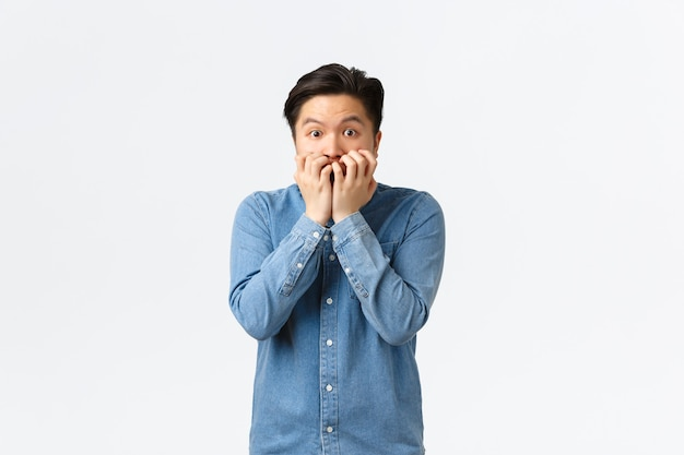 Scared asian guy shivering from fear and biting fingersnails, looking afraid and insecure at camera. frightened man in panic stare anxious, witness terrible accident, watching horror movie.