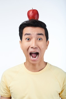 Scared asian man with red apple