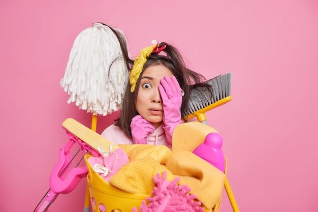 무서워 아시아 여자 얼굴에 손을 유지 매우 더러운 방을 청소하기 시작하는 것을 두려워하는 청소 도구로 둘러싸인 카메라에 겁 먹은 모습은 분홍색 스튜디오 벽에 고립 된 집에서 세탁을합니다