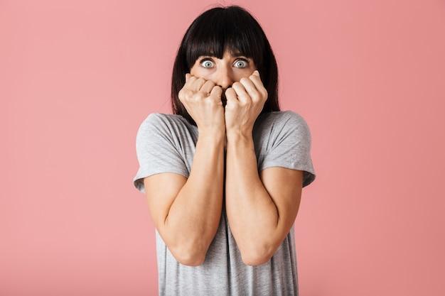 Испуганная привлекательная молодая брюнетка женщина, стоящая изолированно над розовой стеной
