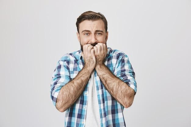 怖がってひげを生やした男が爪を噛んで怖がって