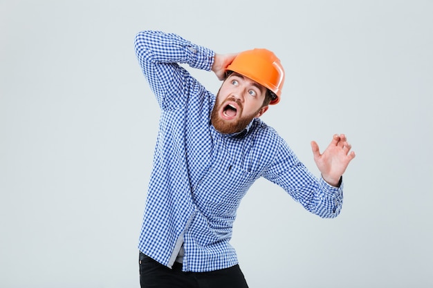 Scared bearded young man in helmet looking up and shouting over white wall