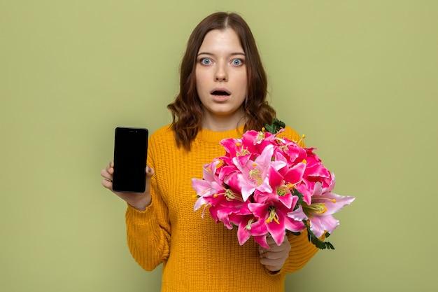 Bella ragazza spaventata il giorno della donna felice che tiene il mazzo con il telefono isolato sulla parete verde oliva
