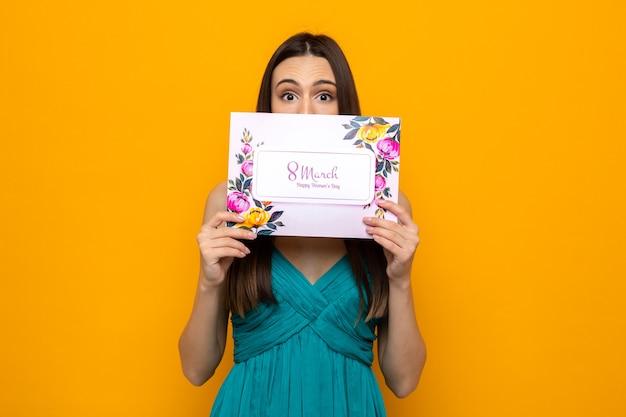 Bella ragazza spaventata durante la festa della donna felice che tiene e il viso coperto con una cartolina isolata sul muro arancione