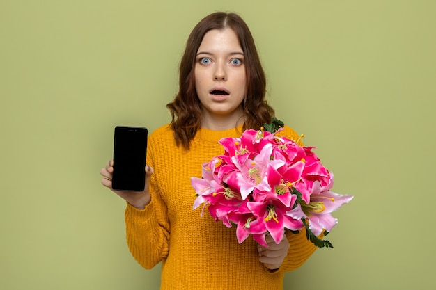 オリーブグリーンの壁に分離された電話で花束を保持している幸せな女性の日に怖い美しい少女