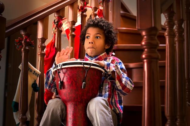 Испуганный черный ребенок с барабаном молодой барабанщик напуган, я думаю, было громко, лучше сделать небольшой перерыв