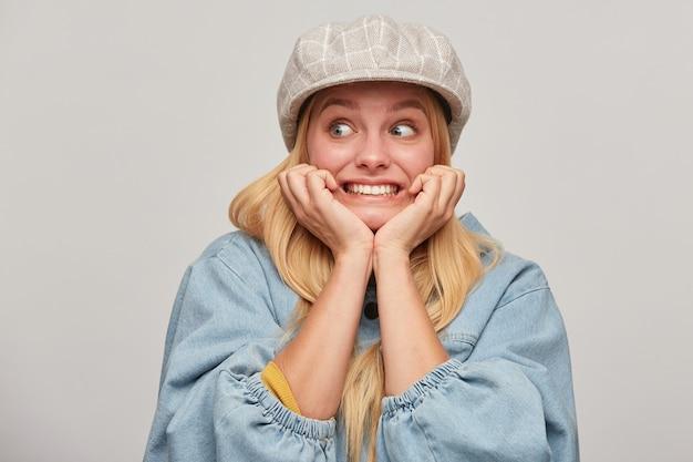 怖がっているブロンドの女性は怖がって怖がって怖がってチャタリング歯を脇に見える