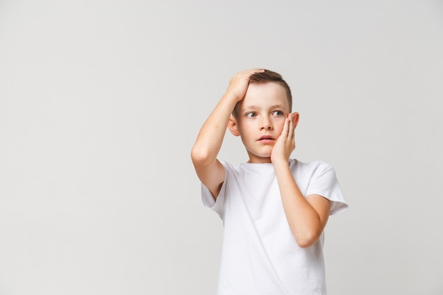 Scared boy in white t-shirt with both hands on head on gray background