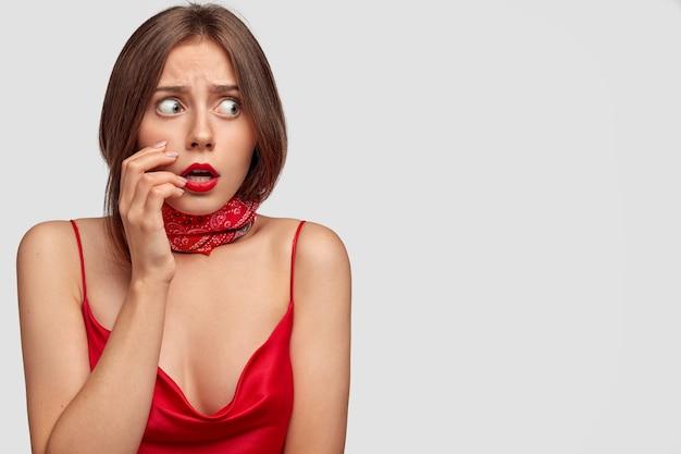 Испуганная брюнетка молодая женщина позирует у белой стены