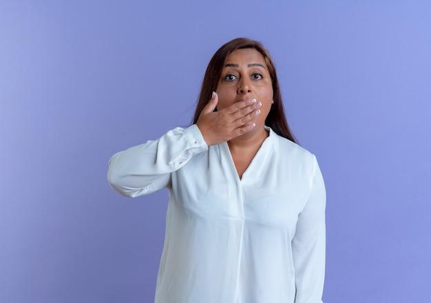 La donna di mezza età caucasica casuale spaventata ha coperto la bocca con la mano isolata sulla parete blu