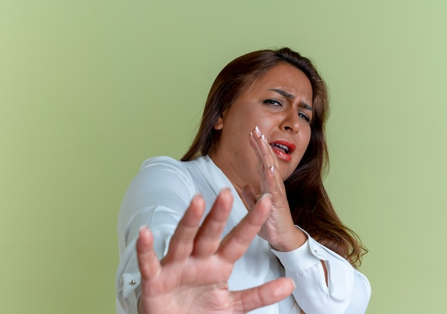 Scared casual caucasian middle-aged woman holding out hands isolated on olive green wall