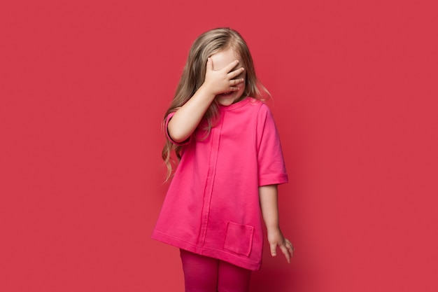 Scared caucasian girl with blonde hair is covering face with palm posing on a red wall
