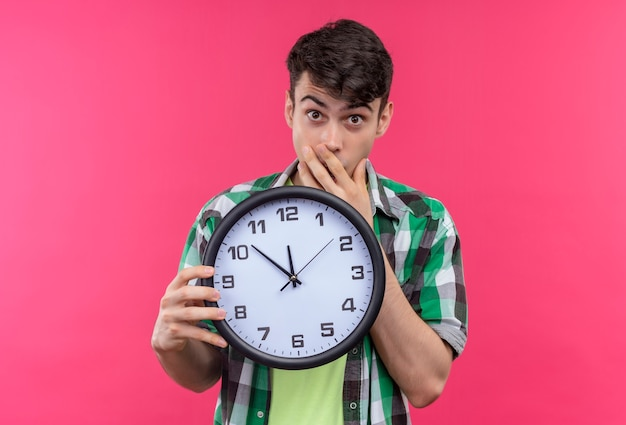 Scared caucasian young guy wearing green shirt holding wall clock and covered mouth with hand on isolated pink background