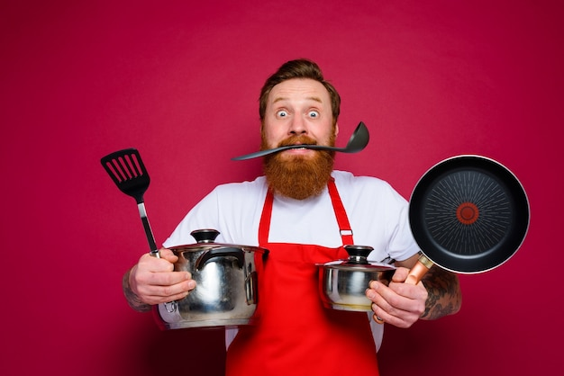 Scared chef with beard and red apron is ready to cook