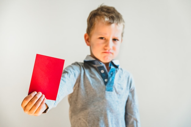 Scared child with red anti bullying card