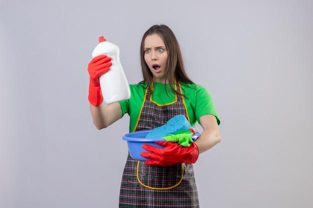 Giovane ragazza spaventata di pulizia che indossa l'uniforme in guanti rossi che tengono gli strumenti di pulizia che esaminano l'agente di pulizia sulla sua mano su fondo bianco isolato