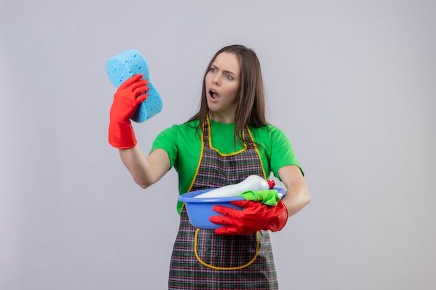 Ragazza spaventata di pulizia che indossa l'uniforme in guanti rossi che tengono gli strumenti di pulizia che esaminano la spugna sulla sua mano su fondo bianco isolato