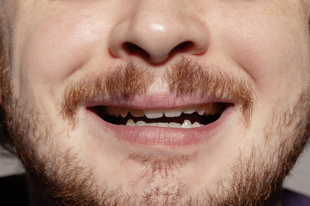 Scared. close up of face of beautiful caucasian young man with redhair beard, focus on mouth.