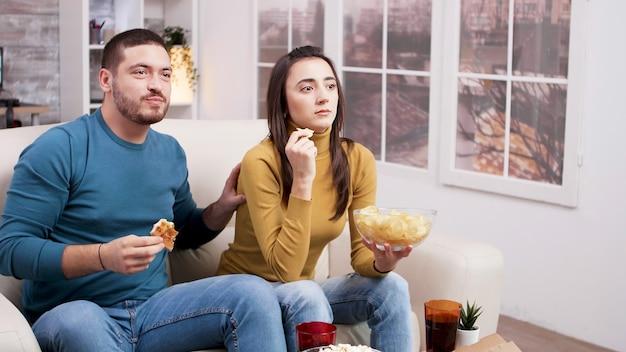 テレビからの映画の恐ろしい瞬間の後の怖いカップル。ピザを食べてソファに座っているカップル。