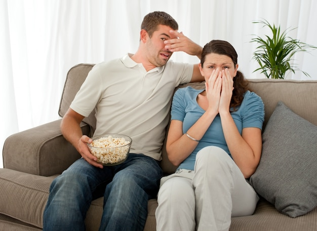 Scared couple eating pop corn while watching a horror movie