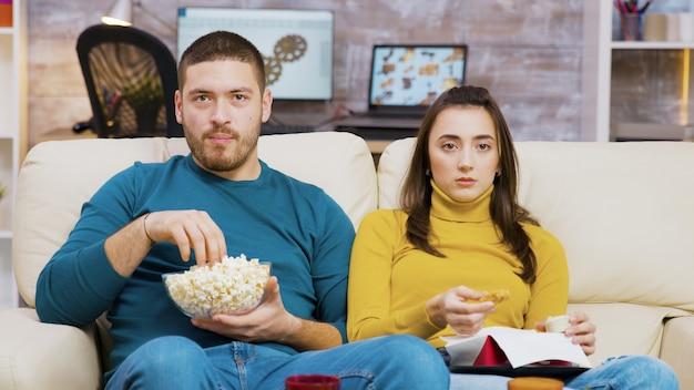 소파에 앉아 피자와 팝콘을 먹고 tv를 보는 겁 먹은 커플. 정크 푸드를 먹는 커플.