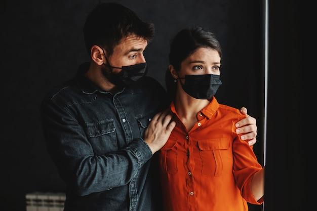 Испуганная пара с масками для лица, стоя рядом с окном и глядя на улицу. блокировка во время концепции вируса короны.