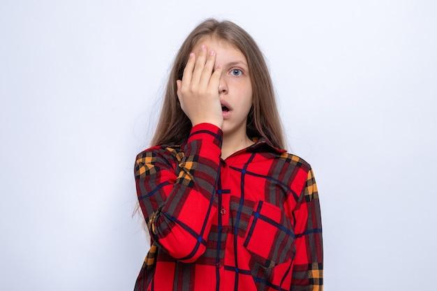 白い壁に隔離された赤いシャツを着た美しい少女の手で覆われた目を怖がらせる