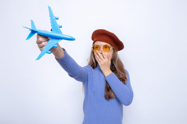 Scared covered face with hand beautiful little girl wearing glasses with hat holding out toy airplane isolated on white wall