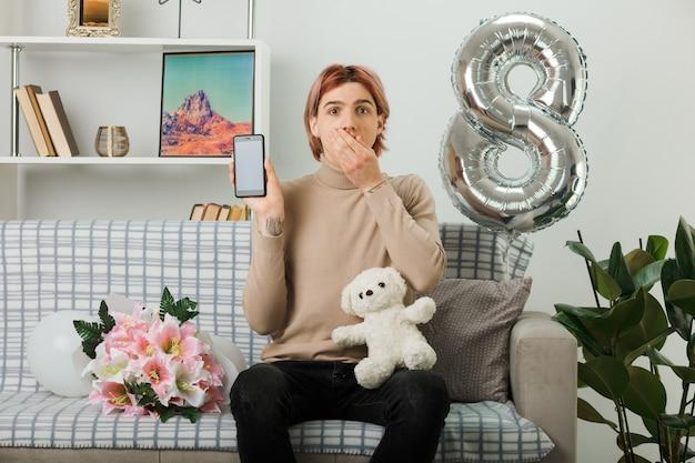 Bocca coperta spaventata bel ragazzo durante la giornata delle donne felici che tiene orsacchiotto con il telefono seduto sul divano nel soggiorno
