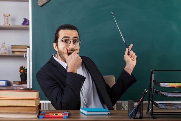 Insegnante maschio con bocca coperta spaventata che indossa occhiali punta con puntatore stick alla lavagna seduto al tavolo con gli strumenti della scuola in classe