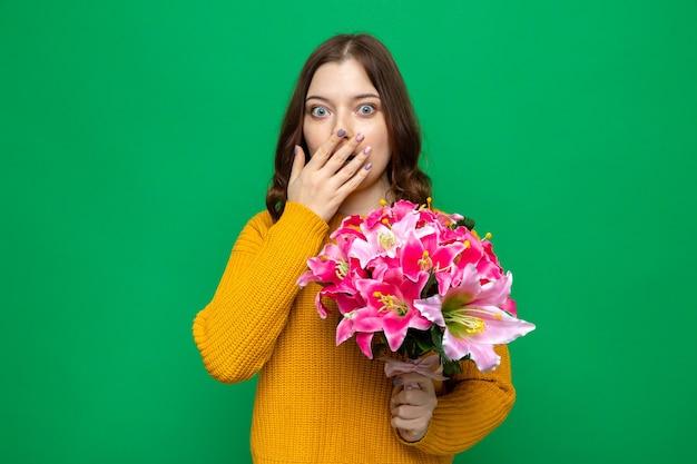 手で覆われた口を怖がらせる花束を保持している美しい少女