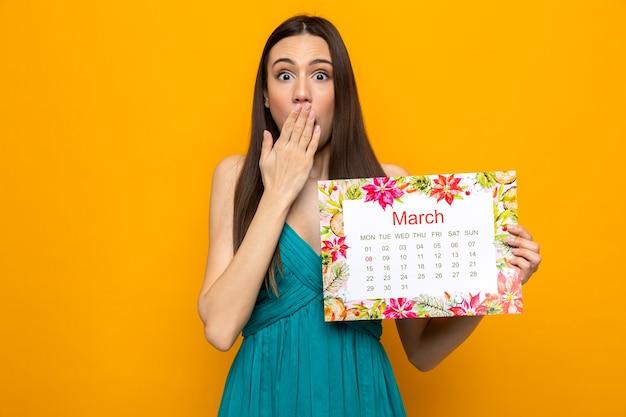 Испуганный прикрытый рот рукой красивая молодая девушка в счастливый женский день держит календарь