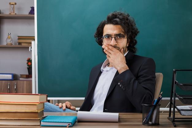 Испуганный прикрытый рот рукой учитель-мужчина в очках сидит за столом со школьными принадлежностями в классе