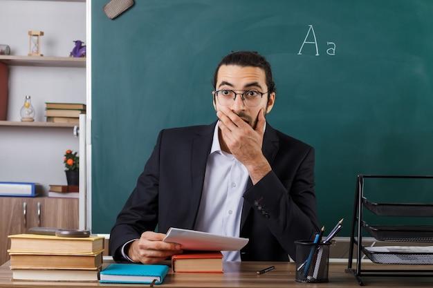 Bocca coperta spaventata con l'insegnante maschio della mano che indossa gli occhiali seduto al tavolo con gli strumenti della scuola in classe
