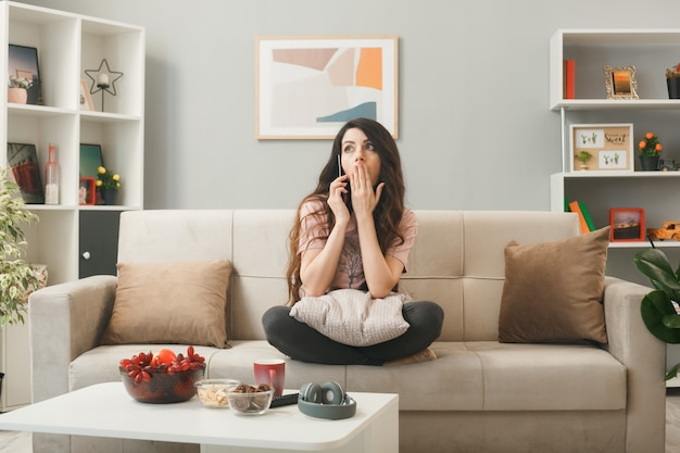 Bocca coperta spaventata con la mano giovane ragazza parla al telefono seduta sul divano dietro il tavolino da caffè in soggiorno
