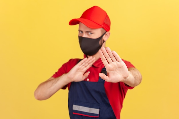 Scared craftsman in uniform and medical protective face mask showing stop