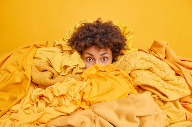 옷 더미로 뒤덮인 겁에 질린 곱슬머리 아프리카계 미국인 여성이 옷장을 청소하고 옷장에서 입을 옷을 찾으려고 카메라를 쳐다본다