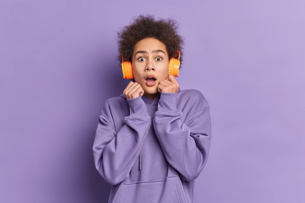 Scared curly haired woman stares with omg expression reacts on something horrible wears stereo headphones for listening music dressed in casual hoodie.