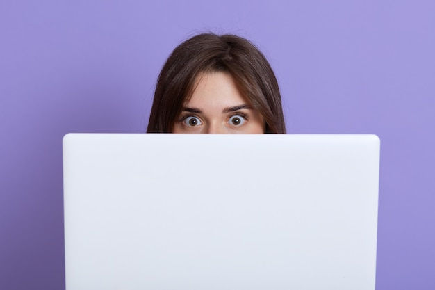 Scared dark haired female hiding behind laptop and looking at camera with eyes full of fear, being afraids of something, wants somebody do not see her, isolated over lilac wall.