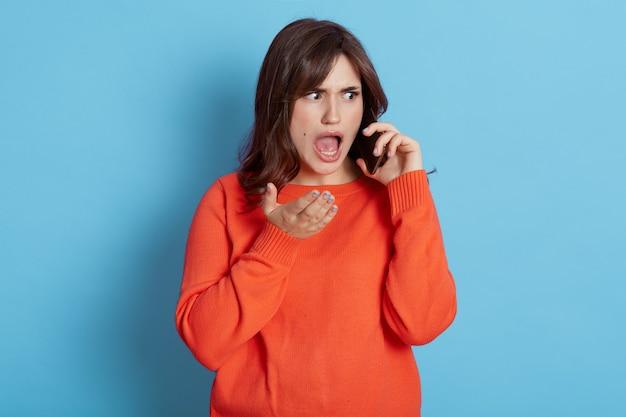 Напуганная темноволосая женщина задыхается от страха, испытывает шок от полученных новостей, смотрит в сторону с широко открытым ртом, разговаривает по смартфону, понимает, что у нее большая проблема, носит оранжевый джемпер.