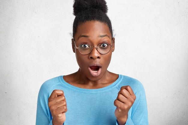 Испуганная темнокожая африканка с кудрявыми волосами выражает удивление и шок, активно жестикулирует и сжимает кулаки от неожиданности.